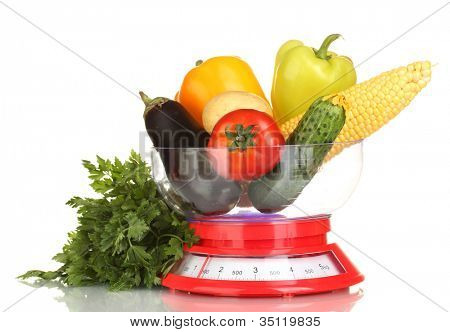 ripe fresh vegetables in the kitchen scales isolated on white