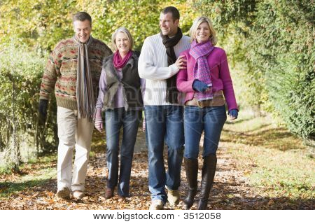 Two Couples Walking Outdoors In Park Smiling
