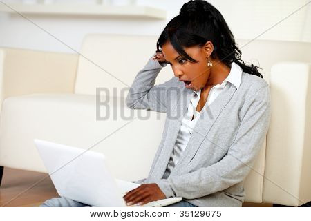 Surprised Young Woman Reading A Message On Laptop
