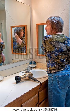 Middle Aged Woman Fixing Her Hair In Bathroom Mirror