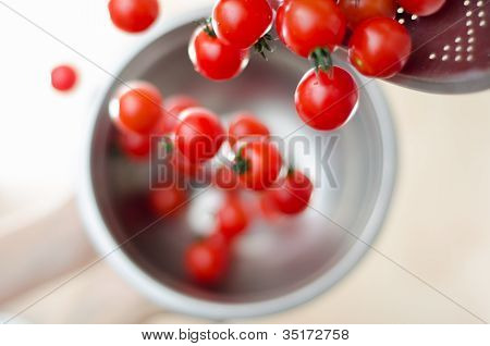 Cherry Tomatoes Tumbling From Metal Colander Into Metal Pan
