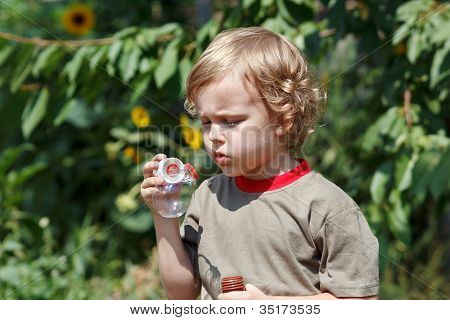Little cute boy playing with bubbles outdoors on a sunny day
