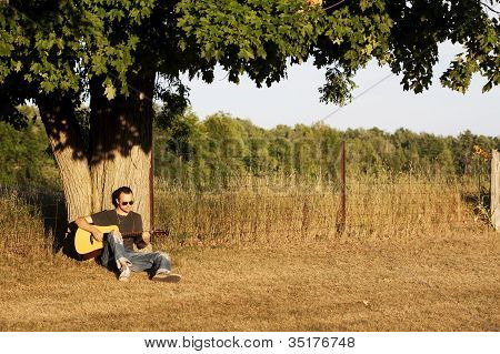 Guy Playing Guitar At Sunset Under Maple Tree In The Country