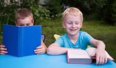 8-year And 6-year Old Boys Reading Books And Smiling