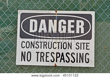 Danger, Construction Site, No Trespassing As Warning Message On Metal Grid