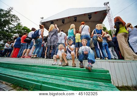 MOSCOW - JUN 23: Unidentified children sit on steps and applaud at concert of Chaif rock-band at VII traditional festival Music of Summer in Hermitage Garden, Jun 23, 2012, Moscow, Russia.