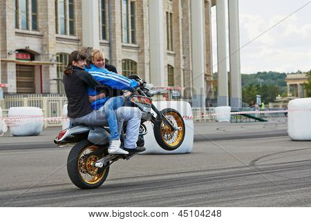 MOSCOW - JUN 30: Member from stuntmen team Avtorodeo Togliatti Trick rides motorcycle with two women during Speedfest at Olympic complex Luzhniki, June 30, 2012, Moscow, Russia.