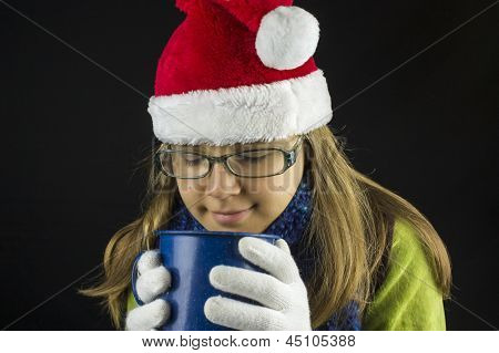 Young girl wearing winter clothing holding cup
