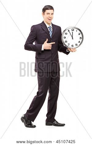 Full length portrait of a youn man in suit pointing on a clock, isolated on white background