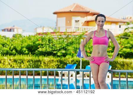 Young smiling woman stands near to handrails at poolside with hands akimbo