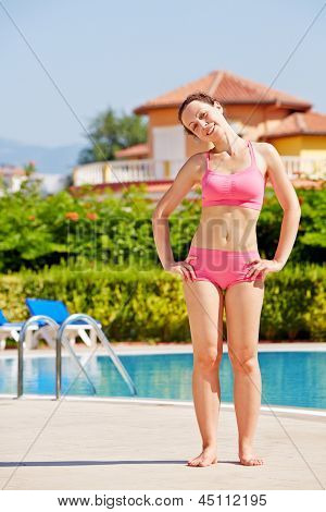 Young smling woman does shoulder-to-shoulder head roll at poolside