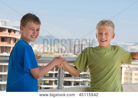 Two smiling boys in colored T-shirts are shake hands on the background of building under construction, focus on right boy.