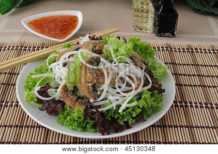 Macarrão de arroz com cogumelos na farinha de rosca em folhas de alface