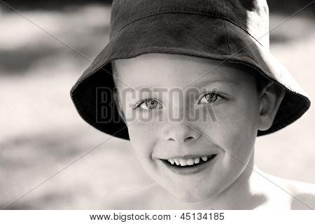 Cute Little Boy Wearing A Sun Hat In The Garden Smiling With Joy