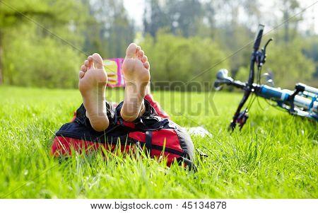 Barefoot Cyclist On A Halt Reads Lying In Fresh Green Grass