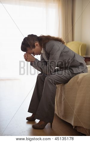 Concerned Business Woman Sitting On Bed In Hotel Room
