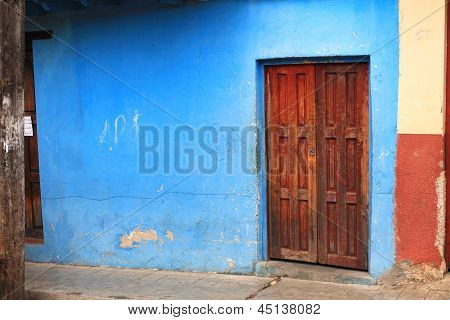 Brown Wooden Door In A Blue Plastered Wall, Mexico