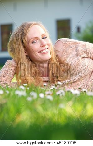 Beautiful Woman Relaxing On Green Grass And Smiling