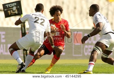 BARCELONA - SEPT, 15: Richard Haughton of USAP Perpignan between two Stade Toulousain players during the French rugby union league match at the Olympic Stadium in Barcelona, on September 15, 2012