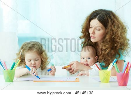 Beautiful mother showing her children how to draw