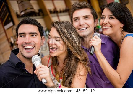 Group of people karaoke singing at a bar having fun