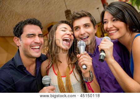 Group of friends having fun karaoke singing at the bar