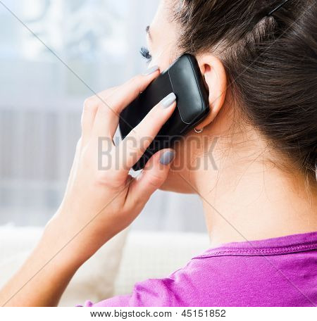 Attractive young brunette woman calling by her cell phone
