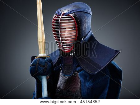Portrait of kendo fighter with bamboo sword. Japanese martial art of sword fighting