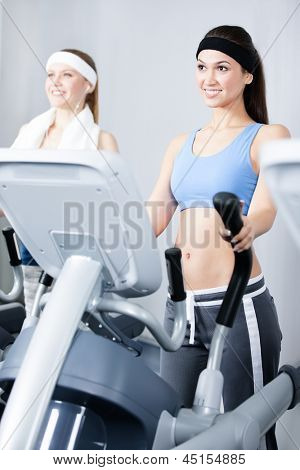 Two young women in sports wear training on simulators in gym