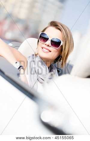 Close up of smiley woman in the car wearing cute sunglasses