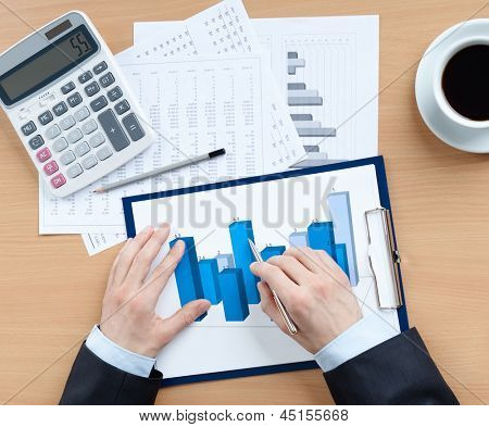 Businessman working with diagrams sitting at the table with calculator, papers and cup of coffee. Top view