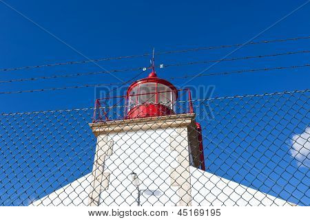 Bright Lighthouse Against Blue Sky Background