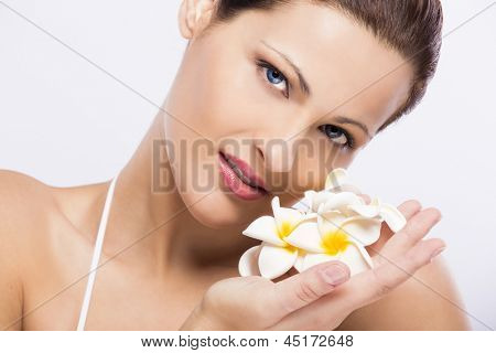 Close up portrait of a beautiful blonde woman holding plumeria flowers close to the face