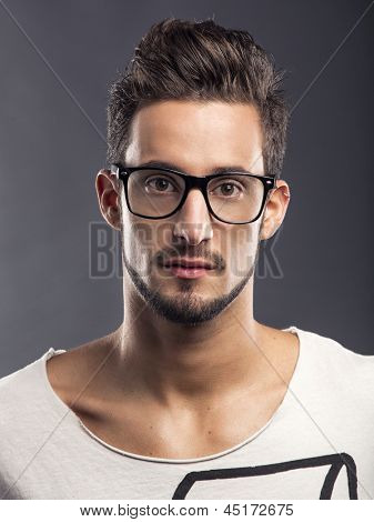Casual portrait of a hansome young man wearing glasses, looking to the camera