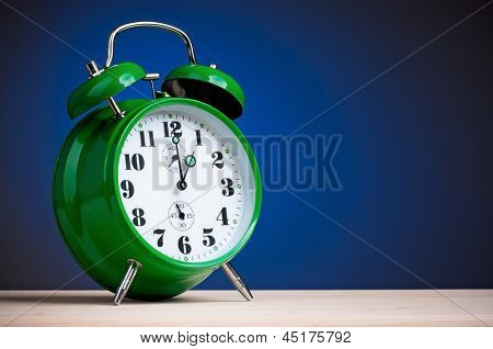 Big green alarm clock on dark blue background