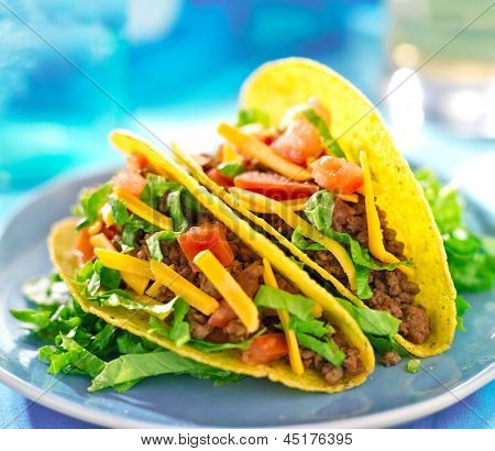 Mexican food - Hard shell tacos with beef, cheese, lettuce and tomatoes