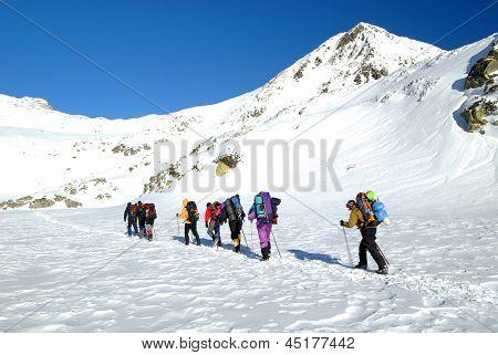 Team of alpinists traversing Bucura Lake in National Park Retezat, Romania
