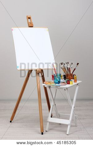 Wooden easel with clean whatman paper and art supplies in room