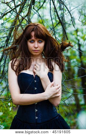 brunette girl witch scary hag eyes wild hair in a black dress be
