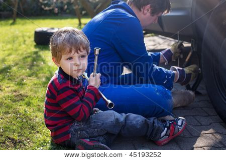 Little Boy And His Father Changing Wheel On Car