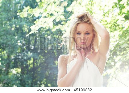 Portrait of young and beautiful blond girl posing outdoor