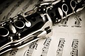stock photo of wind instrument  - Part of a Clarinet laying on notes - JPG