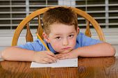 Unhappy child doing his homework at kitchen table at home