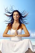 stock photo of prayer  - Attractive young woman meditating on the beach eyes closed - JPG