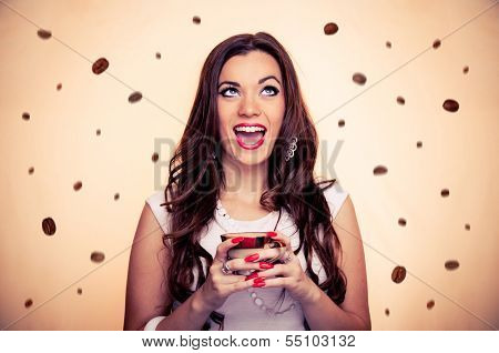 Thrilled beautiful brunette holding cup of coffee while coffee beans falling around her, with beige background