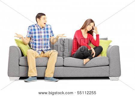 Young heterosexual couple sitting on a couch during an argument isolated on white background