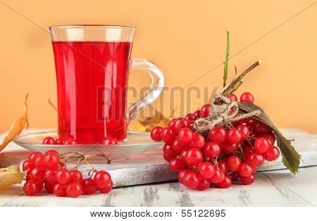 Red berries of viburnum and cup of tea on table on beige background