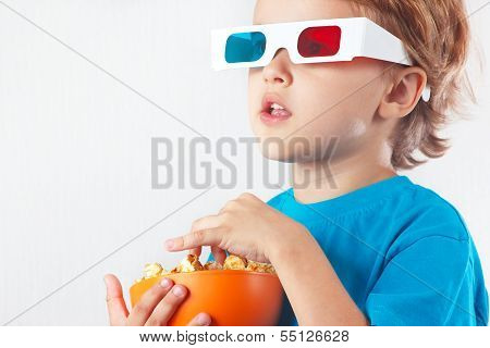 Little blonde boy in 3D glasses with bowl of popcorn