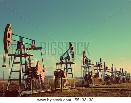 many working oil pumps in row under blue sky - vintage retro style