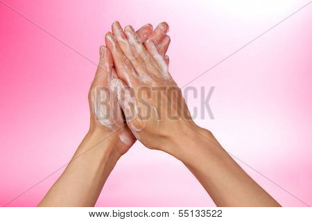 Hands and foam on pink